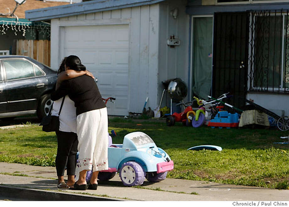 A next door neighbor (right) hugs a woman (neither wanted to be identified) who left the home of Monday's shooting scene at 27744 Seminole Way in Hayward, Calif. on Tuesday, March 6, 2007. Two young girls are in critical condition at Children's Hospital and a young boy was slightly injured in Monday night's shooting.  PAUL CHINN/The Chronicle Photo: PAUL CHINN