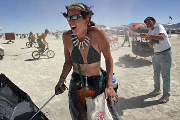 """Michel Reeverts (cq), 35, of Denver, CO reacts at the icy blast of water delivered by """"Just Tom,"""" 49, of Lakeport, CA, who uses melted ice water from a five-gallon jug to cool down burners at Center Camp at Burning Man 2005, Thursday, September 1, 2005 in the Black Rock desert. """"I get 150 hits from five gallons of water and expects to cool off 7000 people this year,"""" he said. burnman2005 Chris Stewart / The Chronicle"""