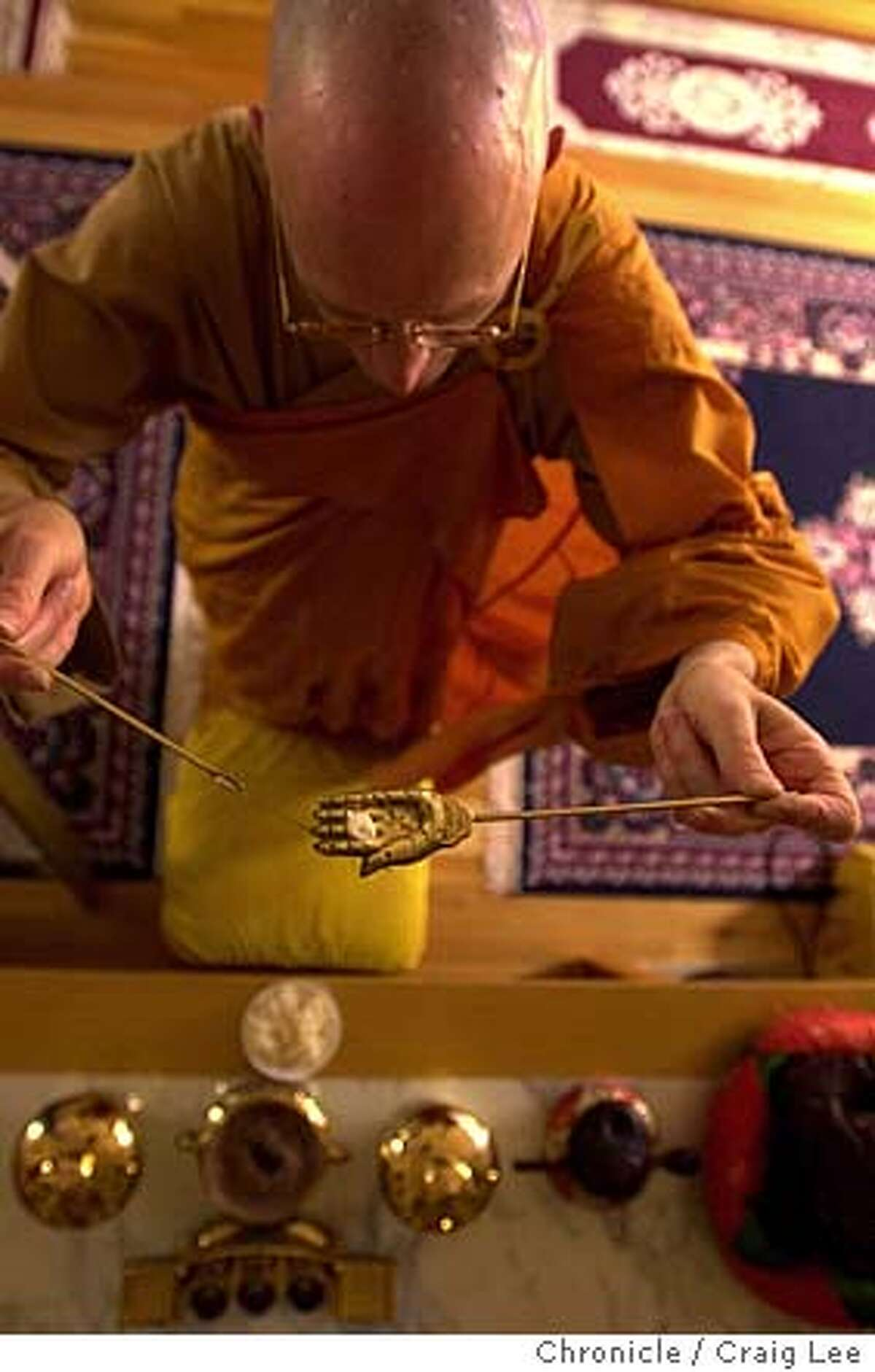 How people pray at meals. This is at the Berkeley Buddhist Monastery at 2304 McKinley Avenue. Photo of Rev. Heng Sure making his ritual offerings to Buddha with 7 grains of rice in the bronze utensils. 5/19/03 in San Francisco. CRAIG LEE/The Chronicle