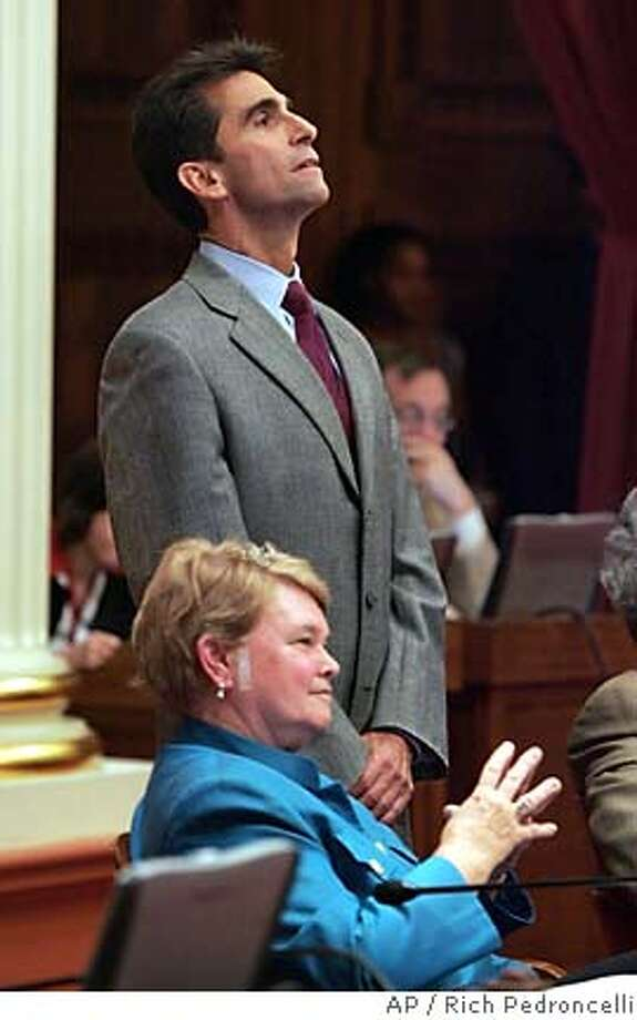 Assemblyman Mark Leno, D--San Francisco, standing, and state Sen. Sheila Kuehl, D-Santa Monica, two of the six gay members of the state Legislature, watch as the votes are counted on for Leno's same-sex marriage bill during the Senate session held at the Capitol in Sacramento, Calif., Thursday, Sept. 1, 2005. By a 21-15 vote, the Senate became the first legislative chamber in the country to approve a bill. The bill will be sent to the Assembly which narrowly rejected a bill in June.(AP Photo/Rich Pedroncelli) Photo: RICH PEDRONCELLI