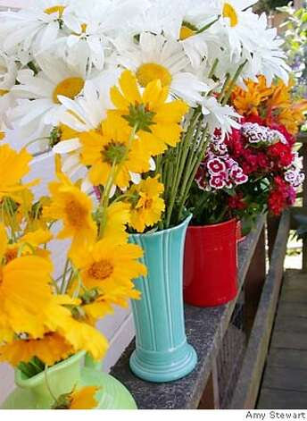 The contrasts of the bright flowers in their pots makes for a lovely sight on the potter's bench. Photo by Amy Stewart