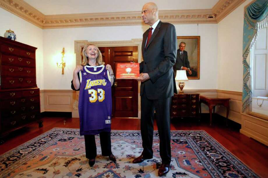 Secretary of State Hillary Rodham Clinton laughs after receiving a Los Angeles Lakers basketball jersey as a gift from global cultural ambassador and former NBA basketball star Kareem Abdul-Jabbar, Wednesday, Jan. 18, 2012, at the State Department in Washington. Abdul-Jabbar will travel the world to engage a generation of young people to help promote diplomacy.   (AP Photo/Jacquelyn Martin) Photo: Jacquelyn Martin