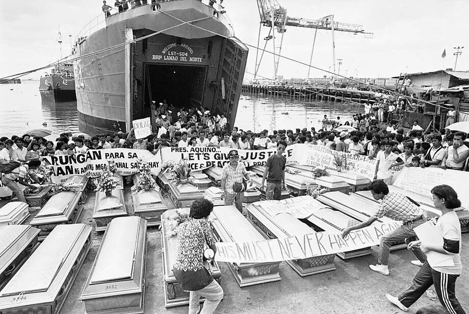 Relatives place a warning streamer on the coffins of victims in the century's worst sea tragedy prior to loading them aboard a Philippine Navy ship Jan. 3, 1988 in Manila, for their last trip home in Leyte province in central Philippines. Authorities recovered only about 108 bodies out of more than 1,500 people aboard a passenger ship which collided with an oil tanker and both sank off Mindoro waters, 100 miles south of Manila. (AP Photo/Bullit Marquez) Photo: Bullit Marquez