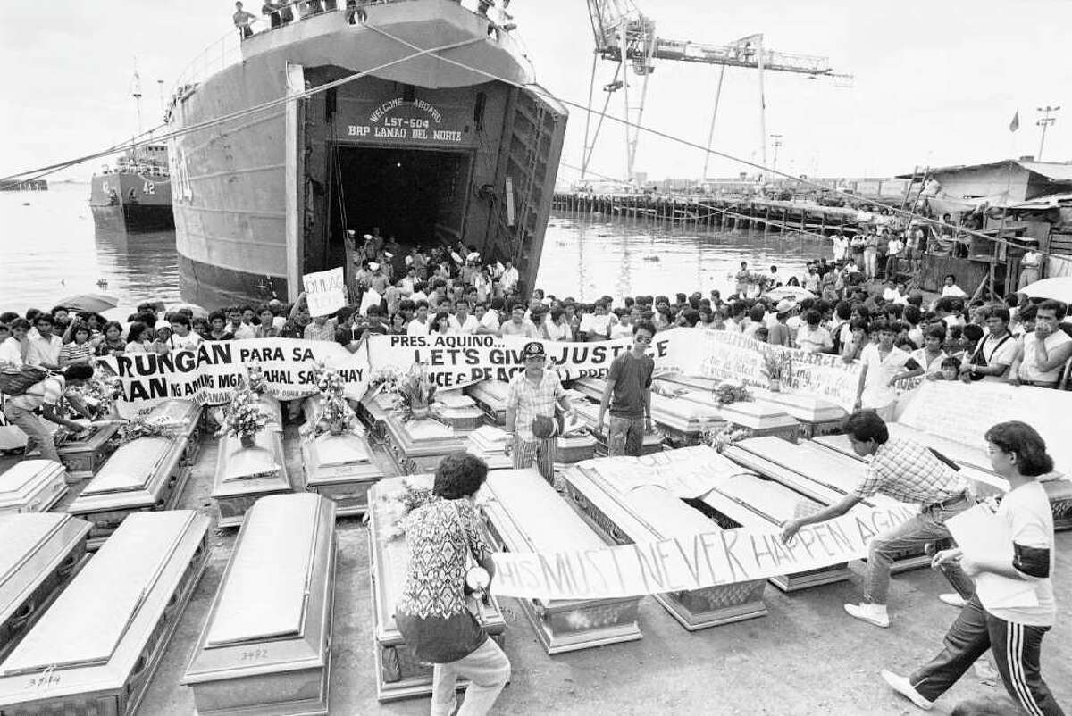 On December 20, 1987, the MV Doña Paz collided with another ship off the coast of the Philippines. Only 21 passengers survived the resulting fire and sinking. Though the official death toll was only 1,565, most estimate that over 4,000 passengers perished in the accident; many were not on the ship's official manifest due to overcrowding. Above: Relatives place a warning streamer on the coffins of victims in the century's worst sea tragedy prior to loading them aboard a Philippine Navy ship in Manila, for their last trip home. Authorities recovered only about 108 bodies.