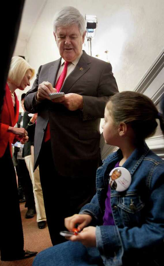 Republican presidential candidate, former House Speaker Newt Gingrich, accompanied by his wife Callista, signs an autographs for a young supporter, Wednesday, Jan. 8, 2012, at the Christ Central Community Center in Winnsboro, S.C. (AP Photo/Pablo Martinez Monsivais) Photo: Pablo Martinez Monsivais / AP