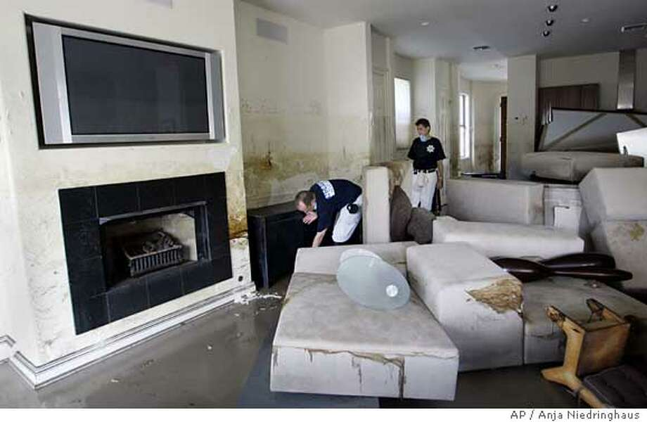 Franco Valobra, left, and his brother Giorgio inspect Franco's home in the Lakefront district of New Orleans on Wednesday, Sept. 14, 2005. Floodwater rose to the middle of the plasma screen television above the fireplace. The home was just built two months ago. (AP Photo/Anja Niedringhaus) Ran on: 09-19-2005 Photo: ANJA NIEDRINGHAUS