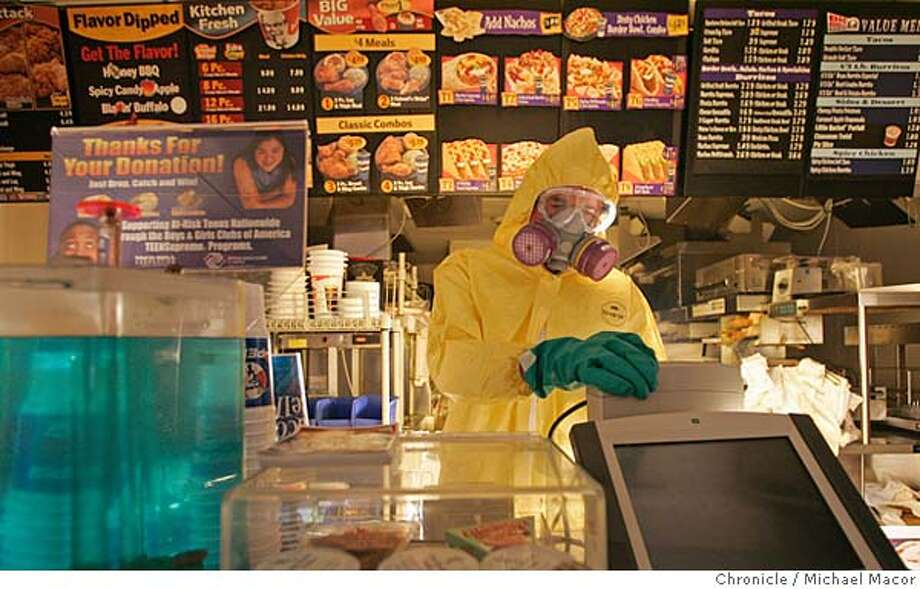 katrina15_111_mac.jpg Tommy Gegenheimer with B & G Foods, wears protective clothing as he begins to clean the KFC/ Taco Bell restaurant on Chartres St. in the French Quarter. The aftermath of Hurricane Katrina that ravaged New Orleans, Louisiana. 9/15/05 New Orleans , La Michael Macor / San Francisco Chronicle Mandatory Credit for Photographer and San Francisco Chronicle/ - Magazine Out Photo: Michael Macor