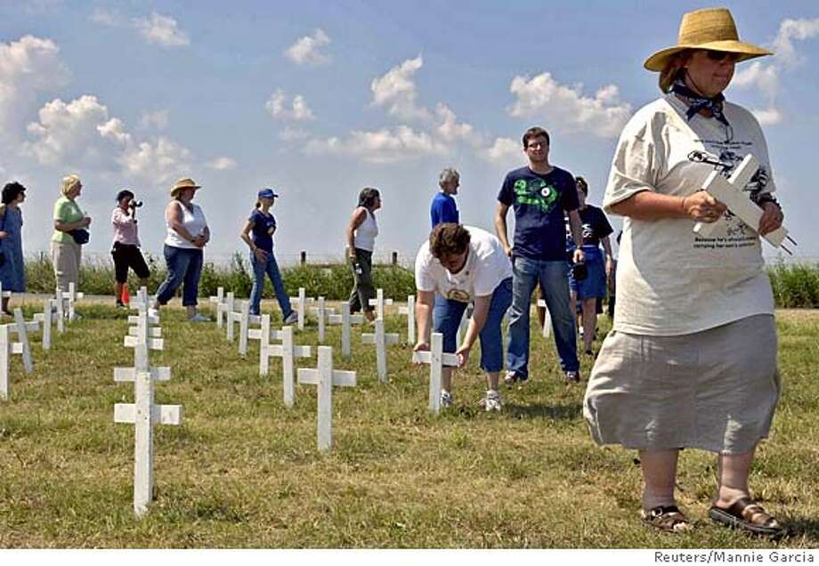 Supporters of Cindy Sheehan collect crosses from a mock graveyard, adjacent to U.S. President George W. Bush's ranch, in Crawford Texas, August 30, 2005. Sheehan and supporters collected all the artifacts as they began closing what has become known as Camp Casey. Reuters/Mannie Garcia 0 Photo: MANNIE GARCIA