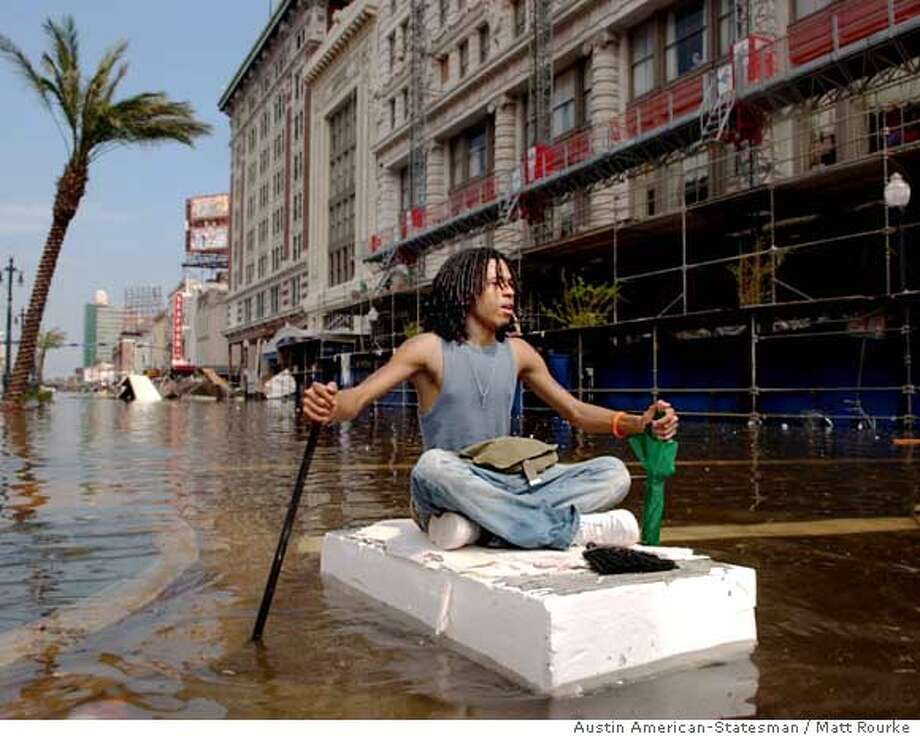 ** ADDS MAGS OUT, , TV OUT ** Jay Williams navigates his way down a flooded Canal St. on a piece of styrofoam Tuesday, Aug. 30, 2005, in New Orleans. (AP Photo/Austin American-Statesman, Matt Rourke) Ran on: 08-31-2005  Jay Williams uses a chunk of Styrofoam for a float as he navigates his way down a flooded Canal Street in New Orleans. Photo: MATT ROURKE