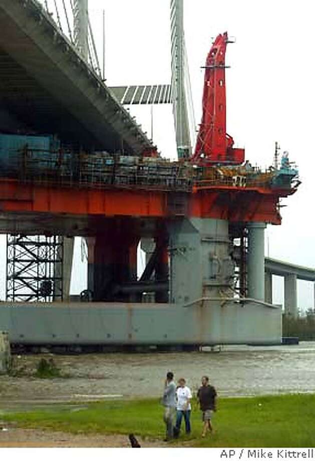 John Welborn, left, Michelle Welborn, center, and Robert Rishel, all of Mobile, Ala., leave the scene where an oil rig that was in dry dock for repairs at a local shipyard rests against the Cochrane-Africatown USA Bridge over the Mobile River Monday, August 29, 2005, in Mobile, Ala. (AP Photo/Mobile Register, Mike Kittrell) Photo: MIKE KITTRELL