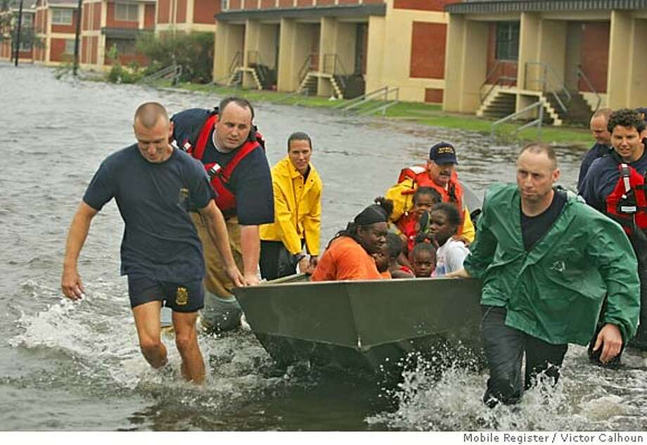 People living in Orange Grove Home in Mobile Monday Aug. 29, 2005 are rescued from the high waters caused by by Mobile Fire Rescue officers.(AP Photo/Mobile Registerr/Victor Calhoun) Photo: VICTOR CALHOUN
