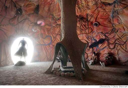 Burners seek shelter from a dust storm inside The Dreamer, which rises from the Black Rock desert at Burning Man 2005. Photo: Chris Stewart