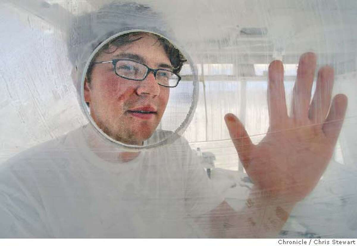 Dicky Davies peers through a mesh screen where he communicates with visitors as he begins his first day in a plastic box at Burning Man 2005, Monday, August 29, 2005 on the playa at Black Rock desert. Davies will spend the entire week in his box - sleeping, eating, writing and whatever - all on public display. burnman2005 Chris Stewart / The Chronicle
