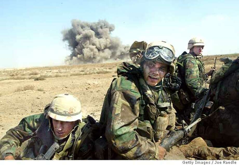 SOLDIERS-C-23MAR03-MN-GET.jpg  NASIRIYAH, IRAQ - MARCH 23: U.S. Marines from Task Force Tarawa duck as a U.S. Marine Cobra helicopter fires a missile that destroys the building behind them while they are pinned down during a gun battle March 23, 2003 in the southern Iraqi city of Nasiriyah. The Marines suffered a number of deaths and casualties during gun battles throughout the city. (Photo by Joe Raedle/Getty Images) Nasiriya Ran on: 08-30-2005  REAL-LIFE COMBAT Marines react after a U.S. missile destroyed the building behind them March 23, 2003, in southern Iraq. Ran on: 08-30-2005 Ran on: 08-30-2005 Ran on: 08-30-2005 Photo: Joe Raedle