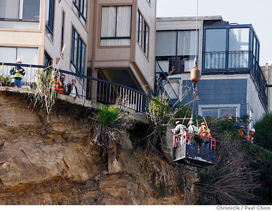 Workers in a basket dangle from a crane to take an up-close view of the deck at 455 Vallejo Street before clean-up of the North Beach slide begins in San Francisco, Calif. on Saturday, March 3, 2007.  PAUL CHINN/The Chronicle Photo: PAUL CHINN