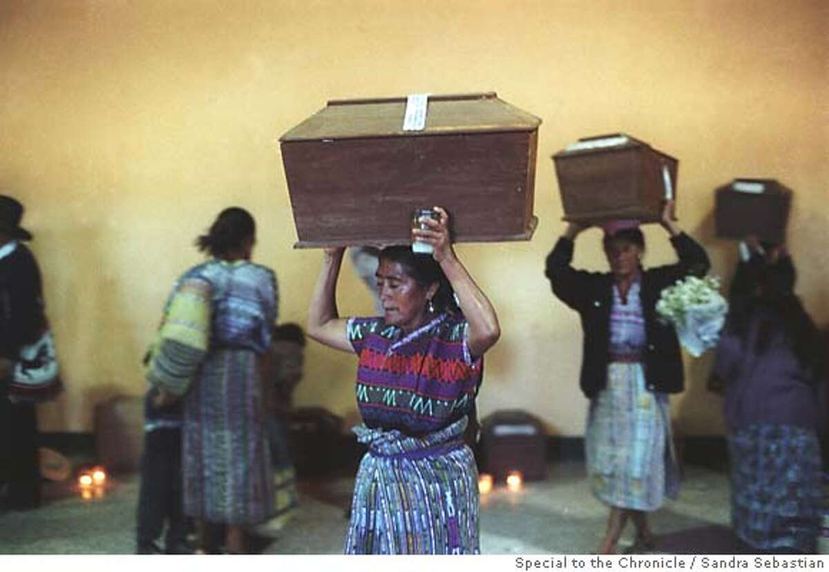 People carry coffins with the remains of victims from Guatemala's civil war that were excavated by forensic anthropologists. Photo by Sandra Sebastian/Special to The Chronicle