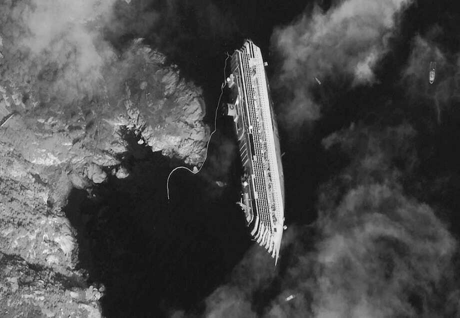This satellite image shows the luxury cruise ship Costa Concordia, which ran aground on Friday, lying on its starboard side just off a Tuscan island. / DigitalGlobe
