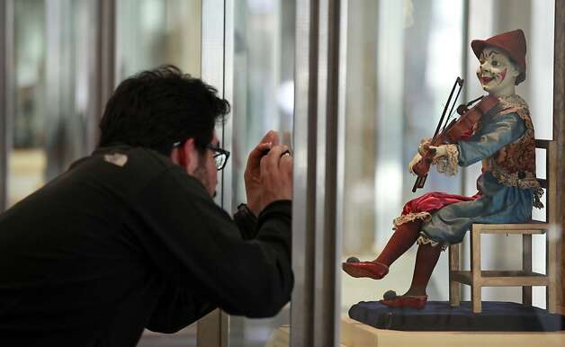 A visitor to San Francisco International Airport photographs a French clown doll exhibit. Forty Million travelers pass through the airport gates annually and are treated to art galleries and a verity of shopping and dinning experiences. Saturday, Jan. 14, 2012, Photo: Lance Iversen, The Chronicle