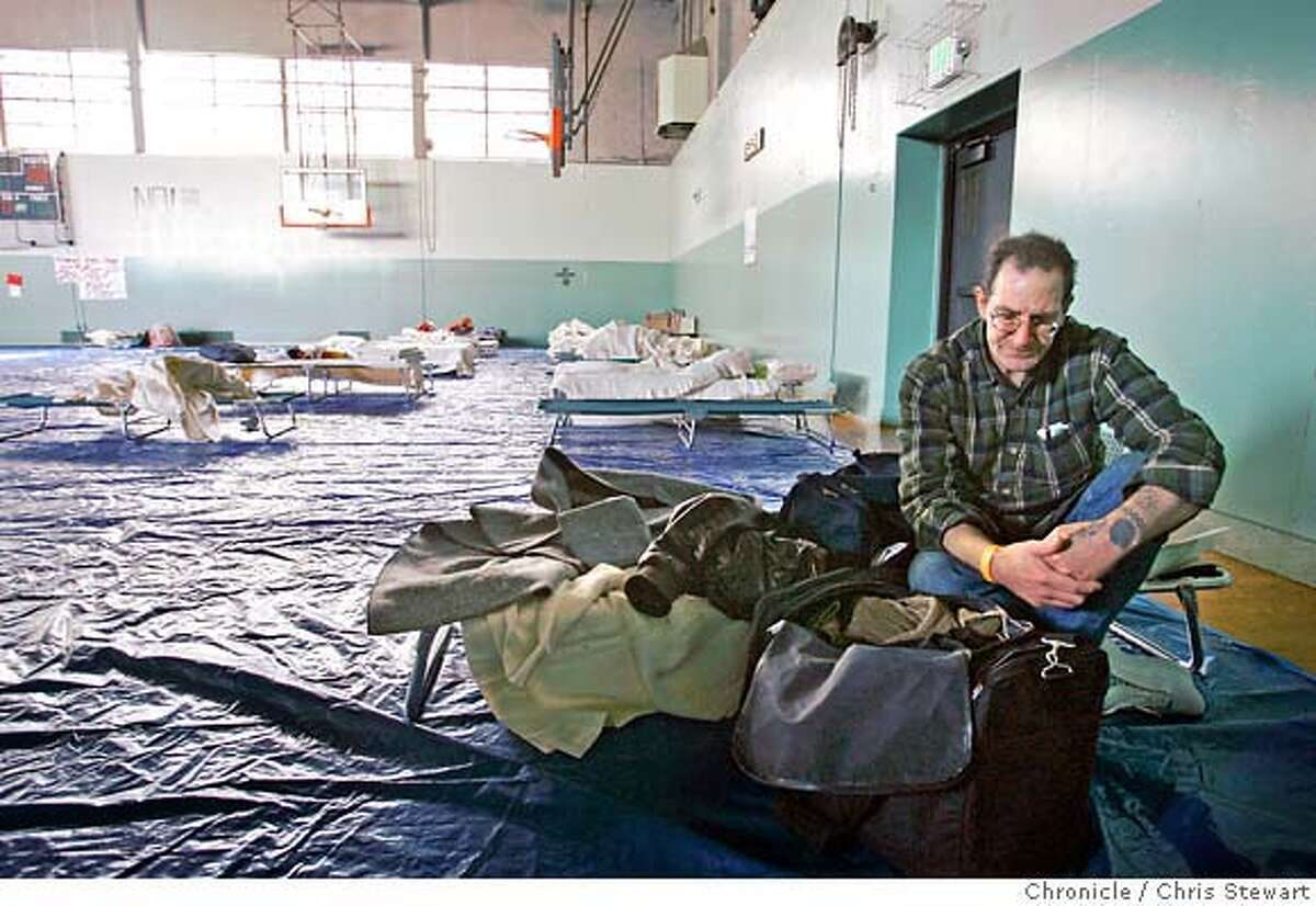 """{filename .} Patrick McDonnal (cq), 49, sifts through his meager belongings in the Chinese Recreation Center gym, 1199 Mason Street, where Red Cross officials have set up a temporary shelter for evacuees affected by Tuesday morning's Telegraph Hill earth slide. McDonnal, a music store employee, is a 12-year resident of 426 Broadway, living on the third, or top floor, of the building. When the early morning slide hit, the rocks and debris piled up against his building so high, """"I could have walked out my window,"""" he said. Photographed February 28, 2007. Chris Stewart / The Chronicle"""