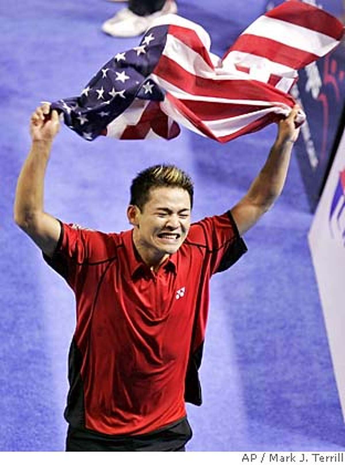 USA's Howard Bach runs with the American flag after he and teammate Tony Gunawan defeated Indonesia's Candra Wijaya and Sigit Budiarto during men's doubles finals at the IBF World Badminton Championships, Sunday, Aug. 21, 2005 in Anaheim, Calif. USA won the match 15-11, 10-15, 15-11. (AP Photo/Mark J. Terrill)