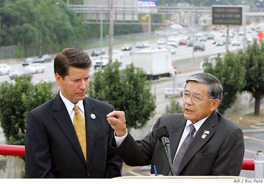 U.S. Secretary of Transportation Norman Y. Mineta, right, and National Highway Traffic Safety Administrator Jeffrey Runge, answer questions Tuesday, Aug. 23, 2005, during a press conference in Atlanta, where they unveiled a plan requiring better gas mileage from sport utility vehicles, pickups and mini-vans. According to Mineta, the proposed new plan for light trucks will save motorists money on fill-ups while improving safety and protecting the economy. The two are flanked by traffic on Atlanta's Interstate 75/85 downtown connector. (AP Photo/Ric Feld) Photo: RIC FELD