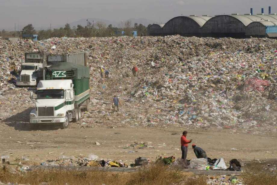 Trailer trucks deposit unprocessed, raw garbage outside the recycling plant (in the background) due to the backlog in the processing of the trash. The Bordo Poniente sanitary landfill and recycling plant is the reception point for the 4000 metric tons of waste generated daily by Mexico City. Photo: Keith Dannemiller / ©2012 Keith Dannemiller