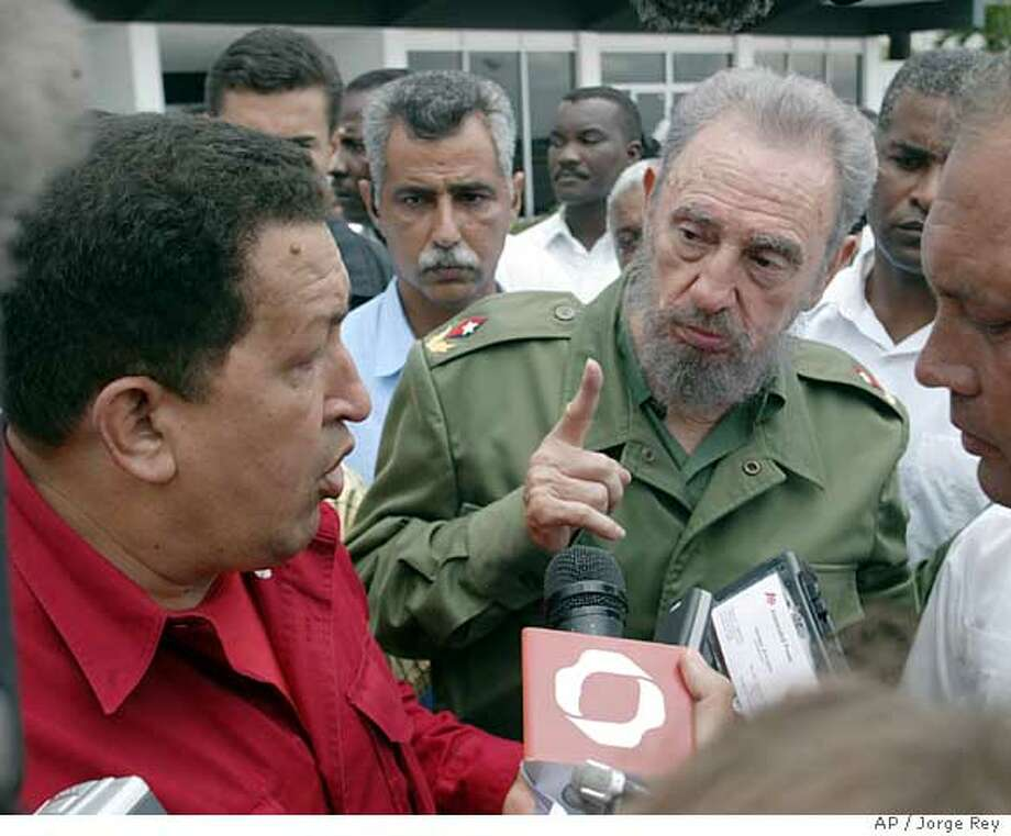 """Venezuelan President Hugo Chavez, left, and President Fidel Castro, speak with the media minutes before Chavez left for Jamaica at Jose Marti international airport in Havana, Cuba Tuesday Aug. 23, 2005. Religious broadcaster Pat Robertson has suggested Monday that American agents assassinate Chavez to stop his country from becoming """"a launching pad for communist infiltration and Muslim extremism.""""(AP Photo/Jorge Rey) Photo: JORGE REY"""