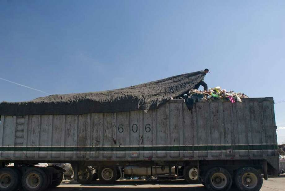 A truck driver covers his load of processed garbage en route to a sanitary landfill. The Bordo Poniente sanitary landfill and recycling plant is the reception point for the 4000 metric tons of waste generated daily by Mexico City. Photo: Keith Dannemiller / ©2012 Keith Dannemiller