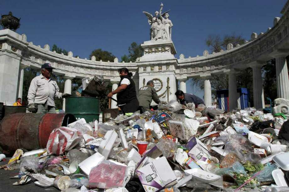 City workers remove piled up garbage that accumulated over the Christmas weekend in front of the Monument to Benito Juarez, one of Mexico's most important statesmen, in downtown Mexico City, Monday Dec. 26, 2011. Garbage disposal workers complain that since last week's official closing of the Bordo Poniente city dump,one of the world's largest, they are backed up trying to get rid of the garbage. Photo: Marco Ugarte, Associated Press / AP