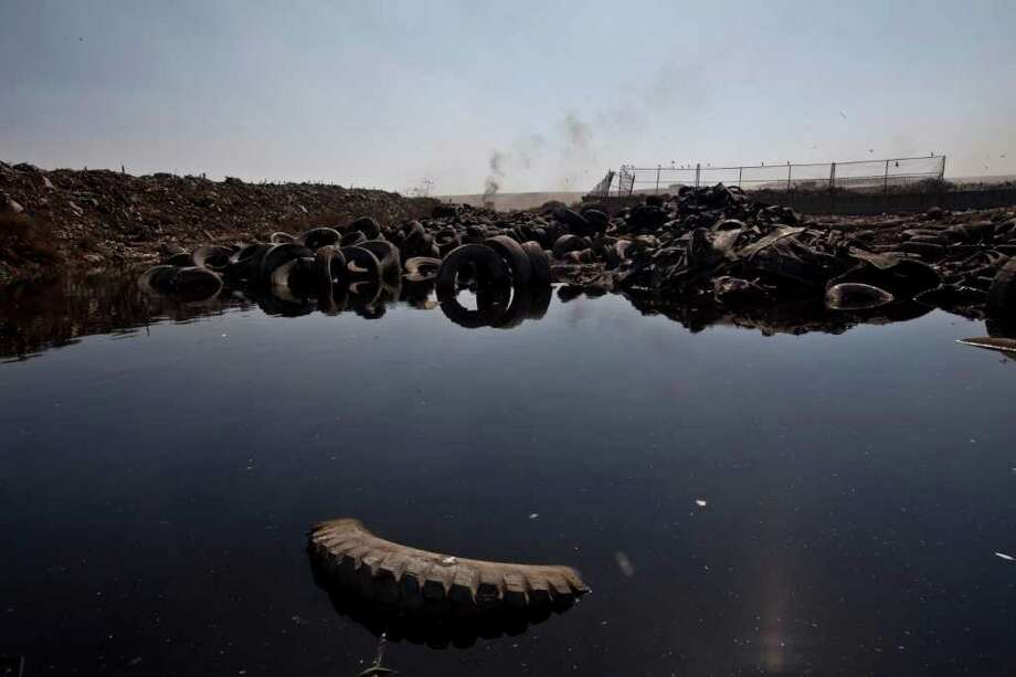 A damaged tires sit in a puddle at the landfill Bordo Poniente on the outskirts of Mexico city, Monday, Dec. 19, 2011. Mexico City will close one of the world's largest dumps by Dec. 31 and will instead turn the garbage from millions of people into reusable materials and energy, Mayor Marcelo Ebrard announced Monday. Photo: Christian Palma, Associated Press / AP