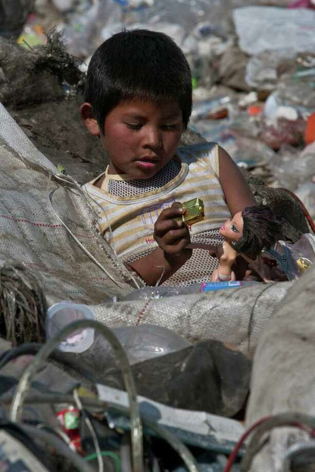 A boy plays among garbage at the landfill Bordo Poniente on the outskirts of Mexico City, Monday, Dec. 19, 2011. Mexico City will close one of the world's largest dumps by Dec. 31 and will instead turn the garbage from millions of people into reusable materials and energy, Photo: Christian Palma, Associated Press / AP