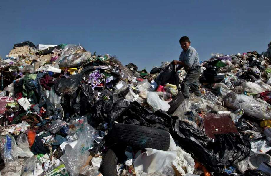 A boy selects garbage to recycle at the landfill Bordo Poniente on the outskirts of Mexico City, Monday, Dec. 19, 2011. Mexico City will close one of the world's largest dumps by Dec. 31 and will instead turn the garbage from millions of people into reusable materials and energy, Mayor Marcelo Ebrard announced Monday. Photo: Christian Palma, Associated Press / AP