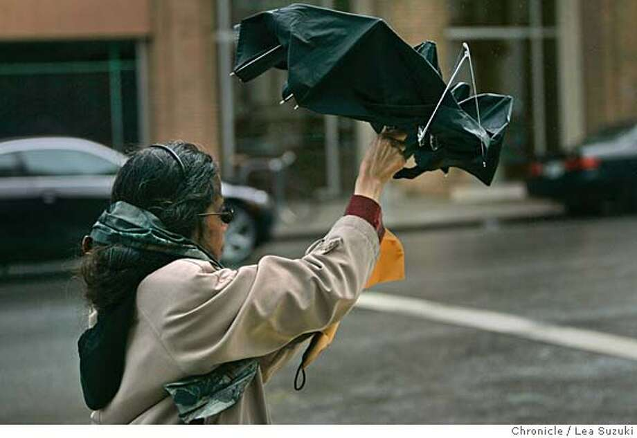 Ramoella Sianipar fights to keep her umbrella open while walking down Howard Street.  Pedestrians battle wind and rain in San Francisco on Feb. 26, 2007. Photo taken on 2/26/07, in San Francisco, CA. Photo by Lea Suzuki/ The San Francisco Chronicle (themselves)cq Photo: Lea Suzuki
