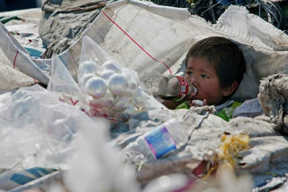 A boy drinks a soda among garbage at the landfill Bordo Poniente on the outskirts of Mexico City, Monday, Dec. 19, 2011. Mexico City will close one of the world's largest dumps by Dec. 31. Photo: Christian Palma, Associated Press / AP