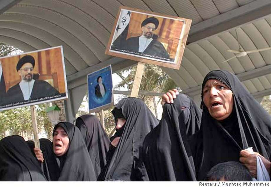 Women hold up posters of Iraqi Shi'ite leader Abdul-Aziz al-Hakim and his brother Mohamad during a protest against the detention of his eldest son Ammar, in Kerbala, 110 km (70 miles) south of Baghdad, February 24, 2007. Iraqis took to the streets of Shi'ite towns and cities on Saturday to protest over the detention by U.S. troops of the eldest son of al-Hakim, one of Iraq's most powerful Shi'ite leaders. REUTERS/Mushtaq Muhammad (IRAQ) 0 Photo: MUSHTAQ MUHAMMAD