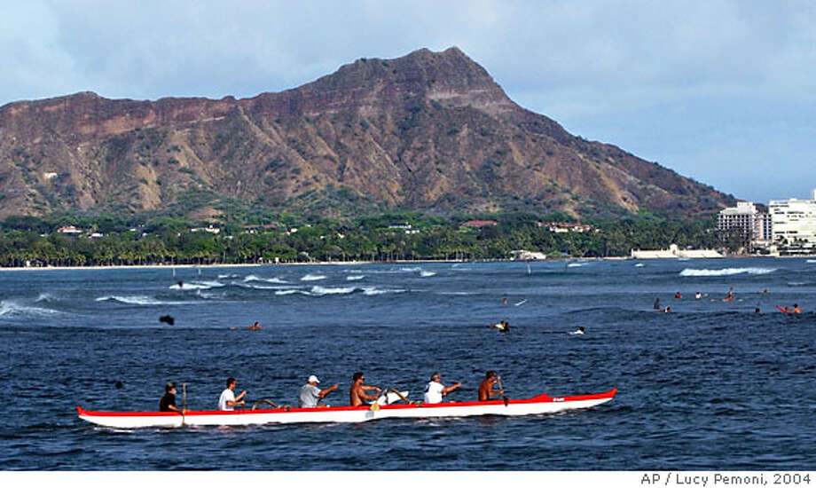TRAVEL ** FOR IMMEDIATE RELEASE **An outrigger canoe paddles past the extinct volcano Diamond Head, June 23, 2004, near Waikiki, in Honolulu, Hawaii. The trek to the summit of the extinct volcano attracts more than 600,000 visitors each year, offering not only breathtaking views of Oahu and the Pacific, but a cheap, memorable, family activity that usually takes less than two hours. (AP Photo/Lucy Pemoni) Photo: LUCY PEMONI