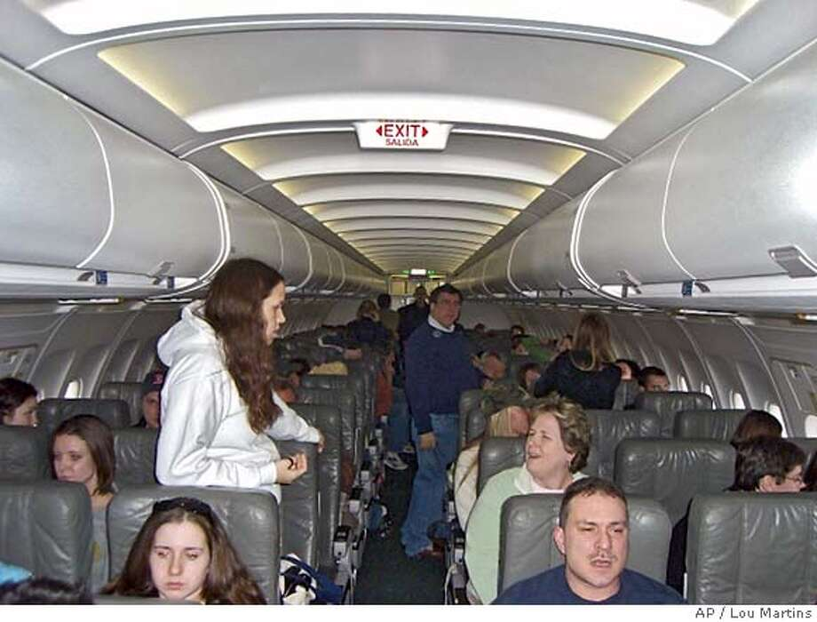 In this photo taken with a cell phone, passengers aboard JetBlue Flight 751 to Cancun walk around the cabin while waiting to take off at John F. Kennedy International Airport in New York, Wednesday, Feb. 14, 2007. Due to a snow storm, the flight was canceled, but not until the passengers waited 8 1/2 hours in the plane. (AP Photo/Lou Martins) **BEST QUALITY AVAILABLE** PHOTO TAKEN WITH A CELL PHONE ** Photo: LOU MARTINS
