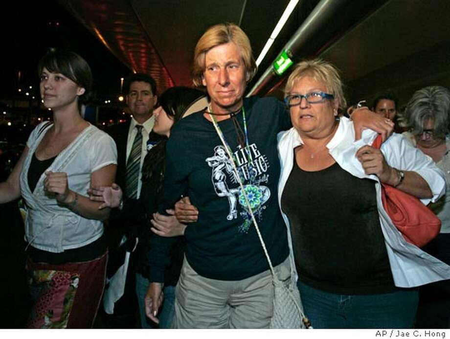 Cindy Sheehan, center, is escorted by unidentified supporters as she arrives at the Los Angeles International Airport on Thursday, Aug. 18, 2005, to visit her 74-year-old mother, who recently had a stroke. Sheehan, mother of Army Spc. Casey Sheehan, who was killed in Iraq, started her roadside vigil Aug. 6 near President Bush's ranch in Crawford, Texas. (AP Photo/Jae C. Hong) Photo: JAE C. HONG