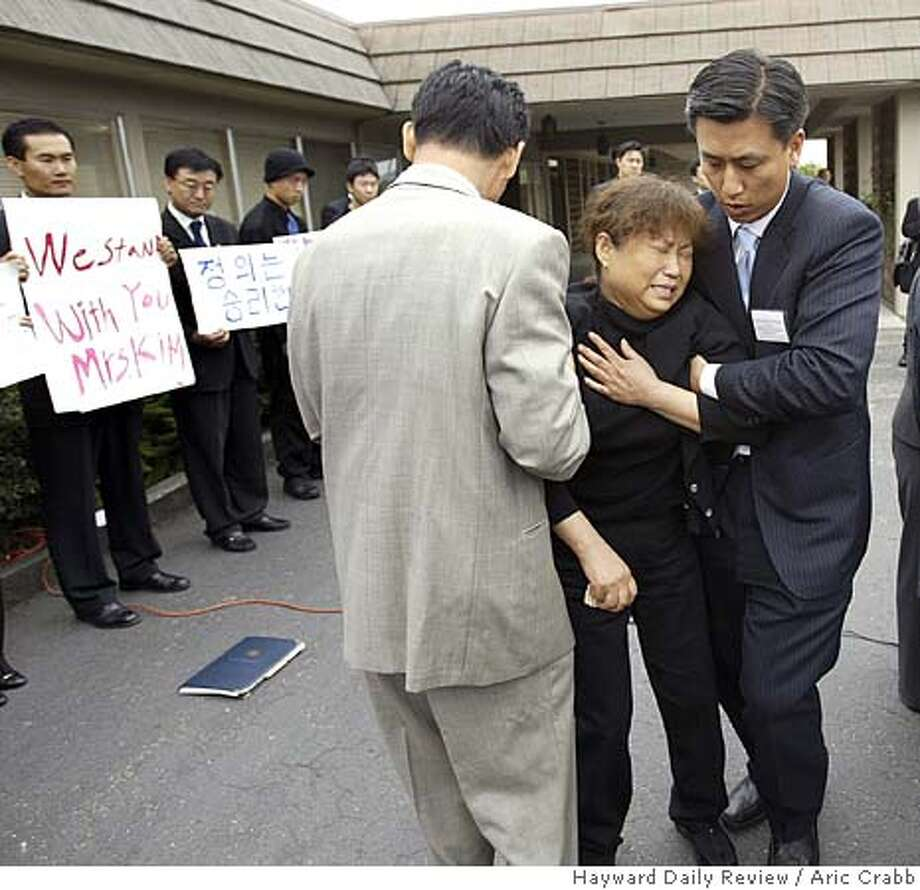 Yang Lim Oh is helped away from a podium by her lawyer Jonathan Bea (right) Friday morning during a press conference at the Jess C. Spencer Mortuary in Castro Valley. Photo by Aric Crabb/Hayward Daily Review 8/19/05 Photo: Aric Crabb/Hayward Daily Review