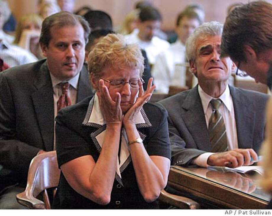 Plaintiff Carol Ernst, center, and her attorneys Randy Moore and Ben Morelli react to the jury's verdict in her favor in her case against Vioxx maker Merck Co. Friday, Aug. 19, 2005, in Angleton, Texas. (AP Photo/Pat Sullivan) Photo: PAT SULLIVAN
