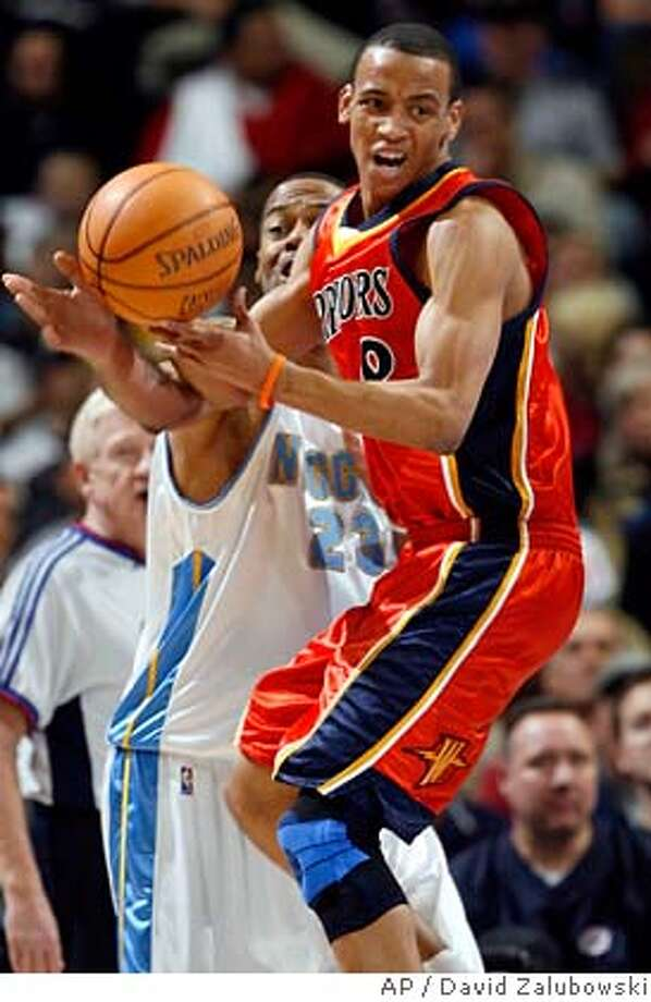 Golden State Warriors guard Monta Ellis, front, pulls down a rebound in front of Denver Nuggets forward Marcus Camby in the third quarter of the Nuggets' 123-111 victory in an NBA basketball game in Denver on Monday, Feb. 12, 2007. (AP Photo/David Zalubowski) Photo: David Zalubowski