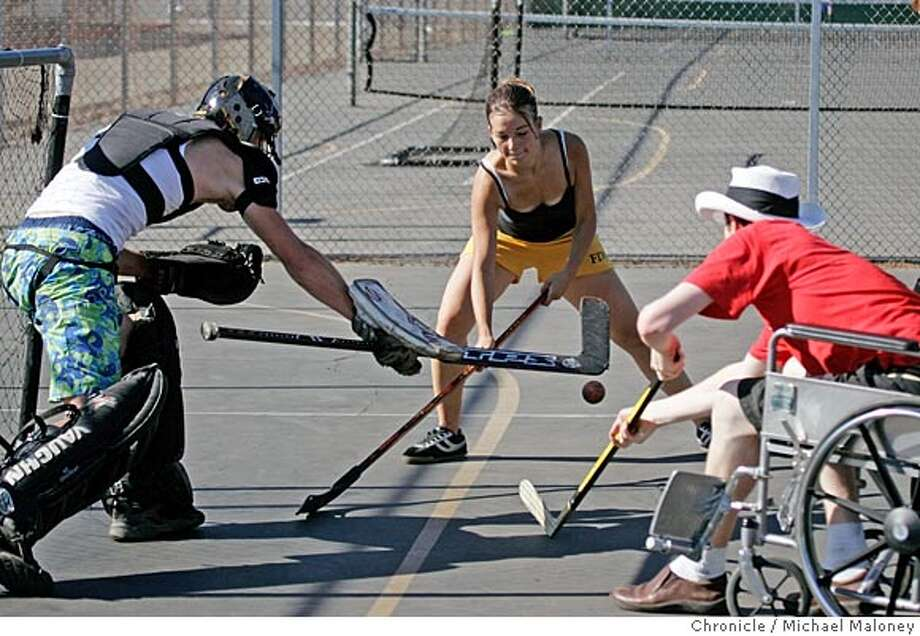 Cindy Libbe (18) and Chris Vallely (21) in wheelchair battle for control of the puck in front of goalie Josh Croghan (19). Members of the East Bay Hockey League play hockey on a tennis court at Canyon Middle School in Castro Valley. The League�s mission is to battle drugs, alcohol and boredom by offering street hockey. The league plays every day and participation is free, including equipment. Photo by Michael Maloney / San Francisco Chronicle Photo: Michael Maloney