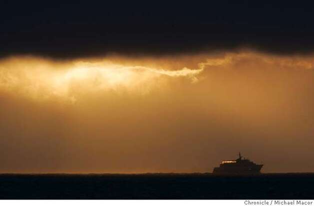 A ferry boat makes it's way North across San Francosco Bay, towards Marin County under a thick layer of fog as the sun sets, filling the sky with warm colors. 7/27/05 San Francisco, Ca Michael Macor / San Francisco Chronicle Photo: Michael Macor