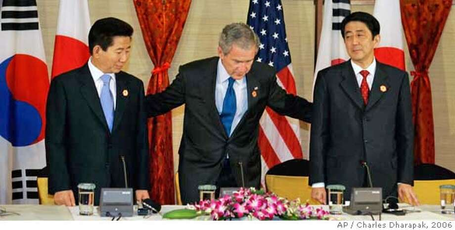 U.S. President George W. Bush, center, invites Japanese Prime Minister Shinzo Abe, right, and South Korean President Roh Moo-hyun to sit at the start of their meeting on the sidelines of the Asian Pacific Economic Cooperation (APEC) summit in Hanoi, Vietnam, Saturday, Nov. 18, 2006. (AP Photo/Charles Dharapak) Photo: CHARLES DHARAPAK