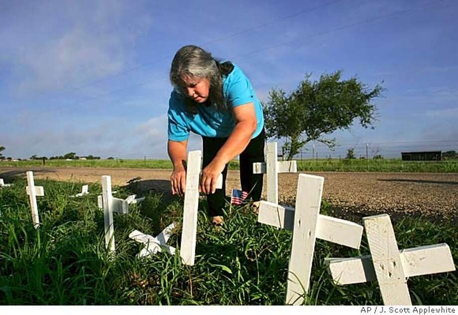 Rowena Jhant, a mother from Waco, Texas, and supporter of President Bush, stops by Prairie Chapel Road at dawn to pick up American flags and white crosses, a makeshift memorial erected by protesters, after a truck tore through them the night before, in Crawford, Texas, Tuesday, August, 16, 2005. Jhant, who disagrees with the anti-war protesters led by 'peace mom' Cindy Sheehan, said she did not feel it was right to drive by and leave the American flags and crosses on the ground without trying to help repair the vandalism. (AP Photo/J. Scott Applewhite) Photo: J. SCOTT APPLEWHITE