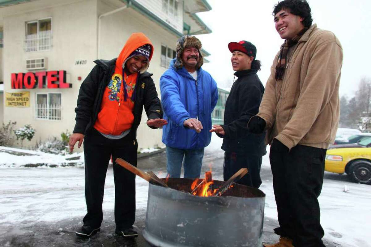From left, Tylynn Shine, Stone Savead, Jazz Crisostomo and Mirigol Poliko warm up around a fire outside a motel on Tukwila International Boulevard on Wednesday, January 18, 2012. After shoveling snow from the parking lot of the motel, the friends used the fire to warm up.