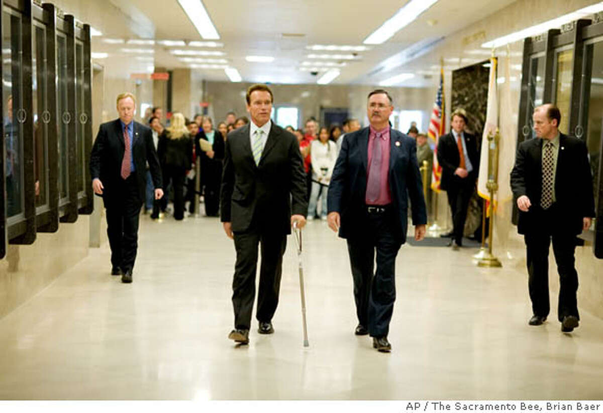 Using a cane, California Gov. Arnold Schwarzenegger walks with Jim Tilton, Secretary of Department of Corrections and Rehabilitation, before holding a news conference to discuss California's prison system, at the state Capitol, Thursday Feb. 22, 2007, in Sacramento, Calif. (AP Photo/The Sacramento Bee, Brian Baer) ** TV OUT, ONLINE OUT, MAGS OUT, NO SALES, MANDATORY CREDIT **