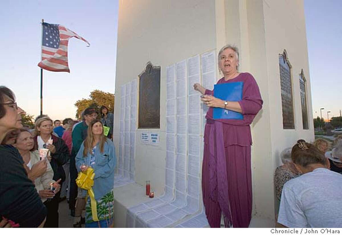 Pleasant Hill, CA. Veterans Memorial Plaza, Boyd Rd. and Contra Costa Blvd. Paula Aiello of San Ramon, a primary speaker, show the list of the Dead from Iraq. A vigil, a testament to Cindy Sheehan. about 200 +_ people gathered at the monument and struggled to hear speakers with out a PA system. Photo/John O'hara