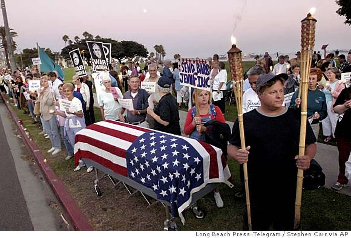 050817- Standing along Ocean Blvd. and Cherry Ave. next to a flag draped coffin, Long Beach resident Jeff Perrin,right, holds up two torches during a candle light vigil for Cindy Sheehan, mother of Army Specialist Casey Sheehan who was killed in Iraq and has kept vigil outside President Bush's ranch in Texas. Over 200 attended the vigil, one of more than 1200 held nation wide. August 17 2005, Long Beach Calif. ( mags out ) Stephen Carr/Press-Telegram