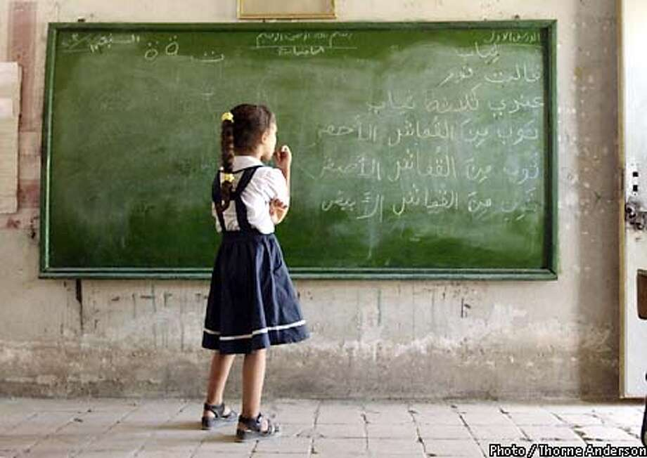 Baghdad, Iraq 05/17/03  A student takes a moment to ponder the problem before writing an answer on the blackboard in the front of her class at the Nidhal Al-Arab primary school in south Baghdad. Many children are kept at home during the day, and school attendance is low amid parents' fears for their children's safety in Baghdad where there has been no effective police force since the American-led invasion. A student who accidentally detonated an unexploded American cluster bomb in the courtyard behind the school raised fears further. Credit: Thorne Anderson/Corbis Sygma Photo: Thorne Anderson